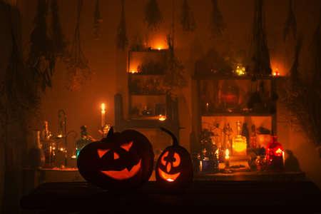 Foto de Halloween pumpkins with candles and magic potions at night indoor - Imagen libre de derechos