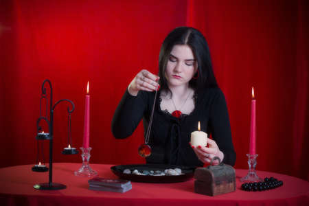 Photo pour young girl in a black dress is engaged in fortune telling on red background - image libre de droit