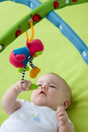 Baby grabbing a hanging down toy