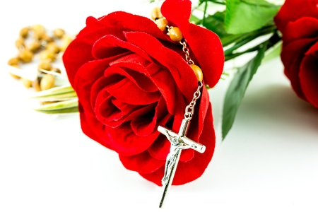 Rosary and rose on a white background