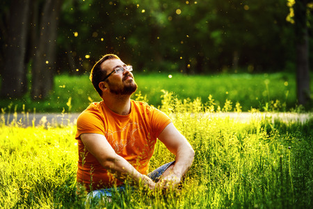 Foto de A happy thoughtful dreamer man is sitting on green grass in a park at sunny summer day and looking into future. Concept of relaxation, wellbeing, lifestyle. - Imagen libre de derechos