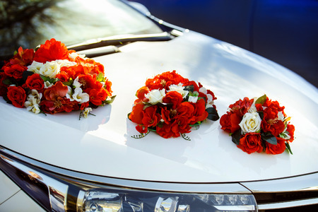 Closeup image of wedding car decoration with red and white flowers bouquet