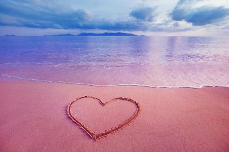 Photo pour Closeup image of heart symbol written on sand at pink sea sunrise background. - image libre de droit