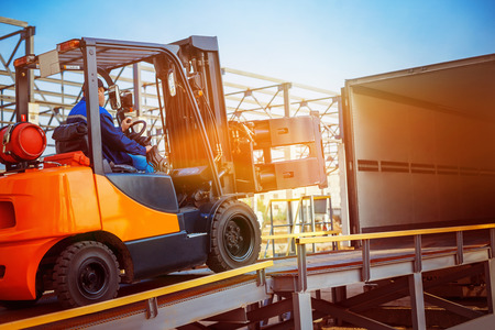 Photo for Forklift is putting cargo from warehouse to truck outdoors - Royalty Free Image