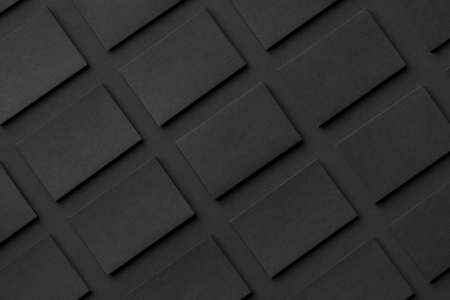 Photo pour Mockup of horizontal business cards stacks arranged in rows at black textured paper background. - image libre de droit