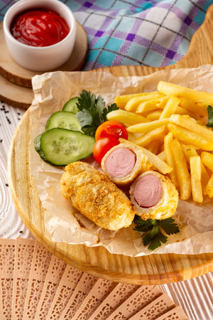 Vertical image of french hot dog with vegetables, fried potato and ketchup on wooden tray at decorated table background.