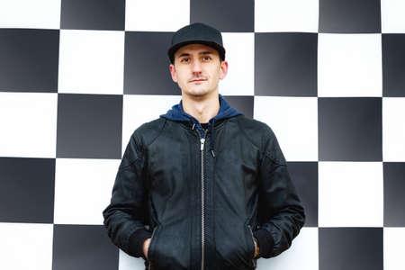 Foto de Vertical portrait of trendy street style dressed young man at checkboard wall background. - Imagen libre de derechos
