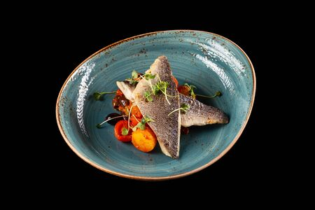 Photo pour Plate of grilled dorado fillet served with roasted vegetables and tomato sauce isolated at black background. - image libre de droit