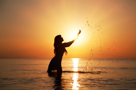 Silhouette of woman making splashes in the rays of the rising sun. Horizontal photo