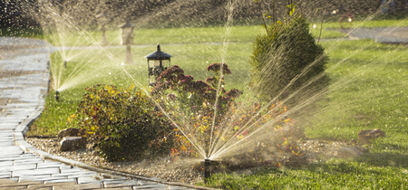 Photo pour A rotating sprinkler spraying a water into the backyard - image libre de droit