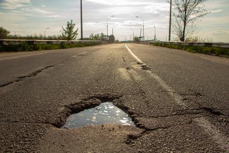 Foto de there are many potholes on the roadway close-up - Imagen libre de derechos