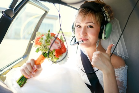 Photo pour Bride inside a helicopter preparing to fly in the headset and with a wedding bouquet showing thumbs up. - image libre de droit