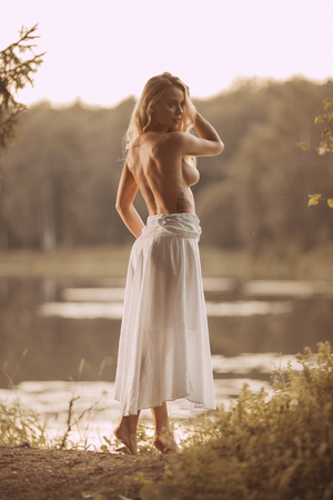 Foto de Sensual young woman with beautiful body standing topless naked or nude by the lake at sunset showing her back - Imagen libre de derechos