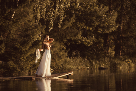 Foto de Attractive young woman with beautiful naked body standing nude on wooden platform by the lake at sunset or sunrise - Imagen libre de derechos