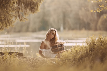 Foto de Attractive young woman with beautiful long blond hair sitting by the lake at sunset and holding picnic basket - Imagen libre de derechos