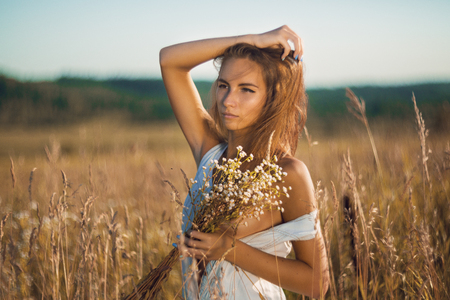 Sensual young girl with slim body standing in field of tall grass in unbuttoned sleeveless jean sundress and covering her naked breasts by bouquet