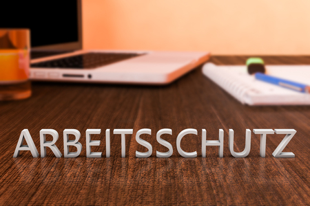 Arbeitsschutz - german word for work safety - letters on wooden desk with laptop computer and a notebook. 3d render illustration.