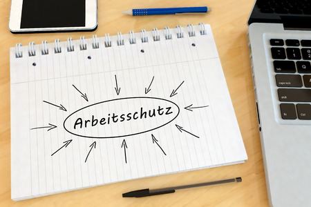 Arbeitsschutz - german word for work safety - handwritten text in a notebook on a desk with laptop and mobilephone- 3d render illustration.