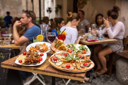 Photo pour Rome, Italy - September 11, 2015: Unidentified people eating traditional italian food in outdoor restaurant in Trastevere district in Rome, Italy. - image libre de droit