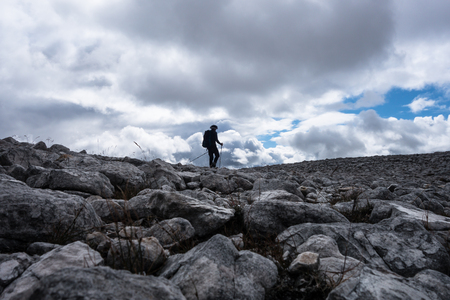 Mountain walker in silhouette against cloudy sky on rock field leading up to top cairn of a Munro in the Scottish Highlands