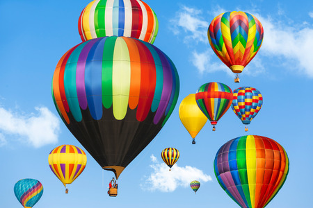 Colorful hot air balloons over blue sky.