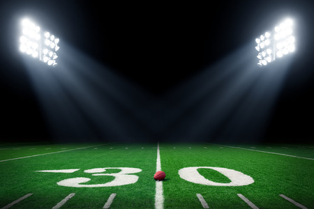 American football field at night with stadium lights