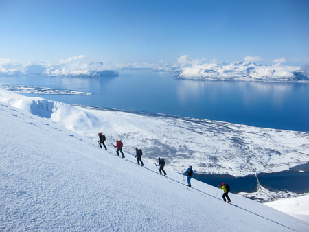 A group of people randonee ski walking high above the fjords. Lyngen Alps, Norway