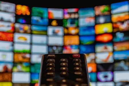 Photo for Video on demand screen with remote control in hand, streaming - Royalty Free Image
