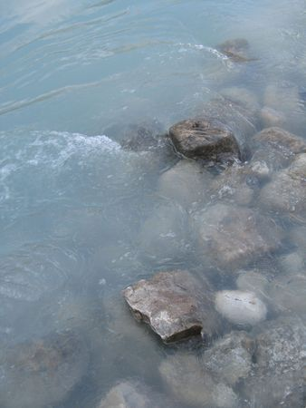 grey polished rocks and green river water