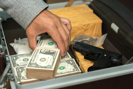 Foto de Drug trafficker holding a lot of cash on hand and use gun pushing drugs to the customer in the Drug dealing, concept about the drug problem - Imagen libre de derechos