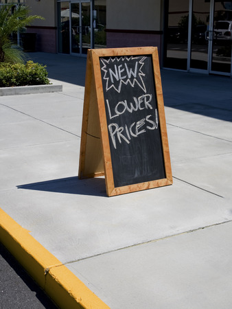 Blackboard sign that says lower prices on sidewalk