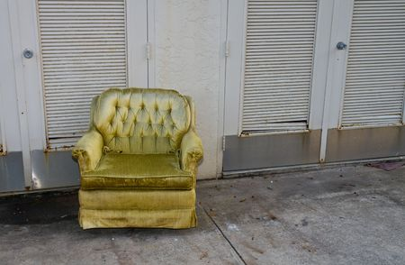 Ugly grungy abandoned yellow armchair in alley