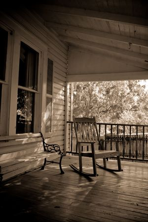Sepia toned old time country porch with rocking chair and bench