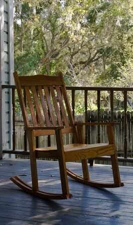 Old wooden rocking chair sitting on a porch