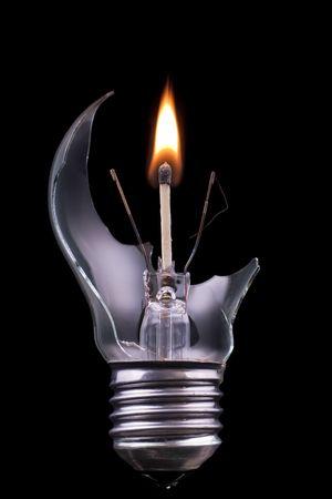 Photo pour A broken lightbulb with a burning match inside - image libre de droit