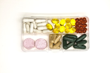 Different pills, medications, the pills in the daily drug medicine organiser drugs closeup on white background.