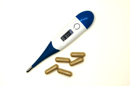 Modern electronic thermometer with pills closeup on white background.