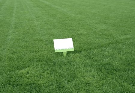 fresh green grass background with a white sign ready to write