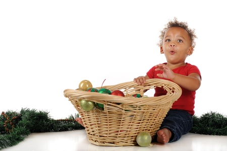 An adorable toddler delighted with a basketful of Christmas bulbs.  One a white background.