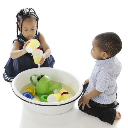 An overhead view of two adorable kis playing with toys in a tub of water   On a white background