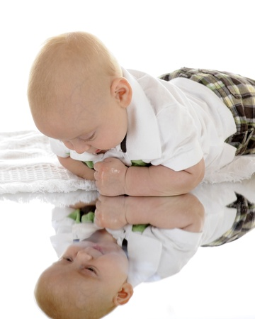 An infant looking at himself in a mirror below him.  On a white background.