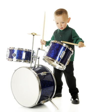 A young preschooler intently drumming on a child-sized drum set.  On a white background.  (Motion blur on lower drum stick.)