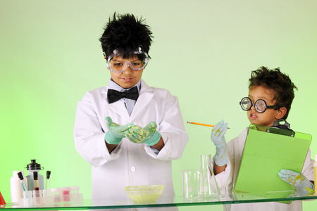 Two biracial brothers with wild hair protective clothing experimenting with solutions together