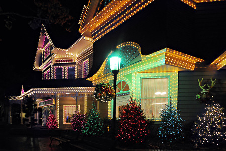 Nioght time image of a large, beautiful home all decked out in lights in celebration of Christmas.