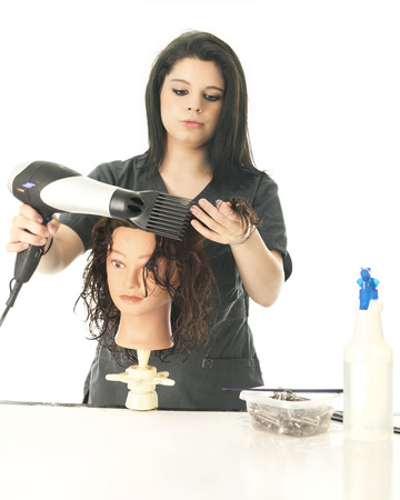 A pretty teen cosmetology student blow-drying her practice head's hair.  On a white background.