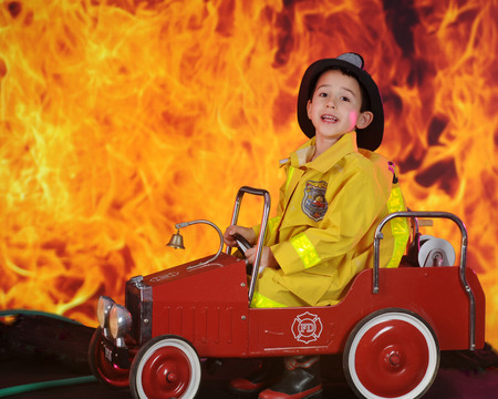 A preschool fireman calling for reinforcements for the huge blaze behind his vintage toy fire truck.
