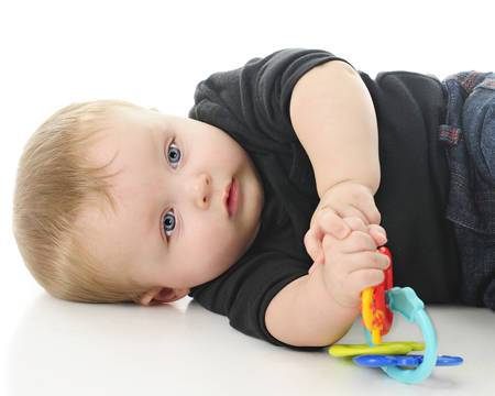 Close-up of an adorable baby boy contentedly laying on the floor with his toy.  On a white background.