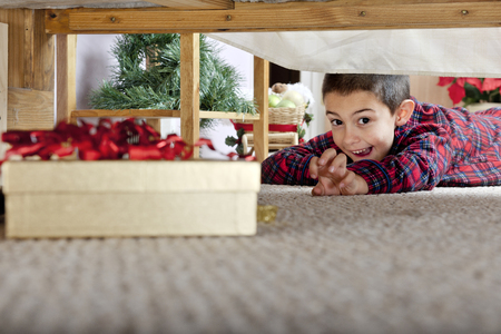 Photo pour A young elementary boy delighted at seeing a boxed gift under his parents' bed. - image libre de droit