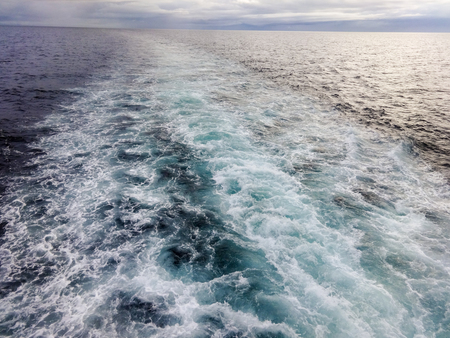 The waves of a boat beyond the horizon