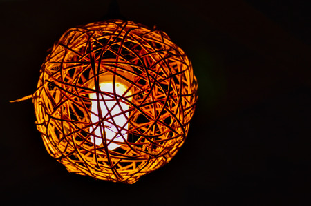 A wood-woven lantern appears golden in the deep black night